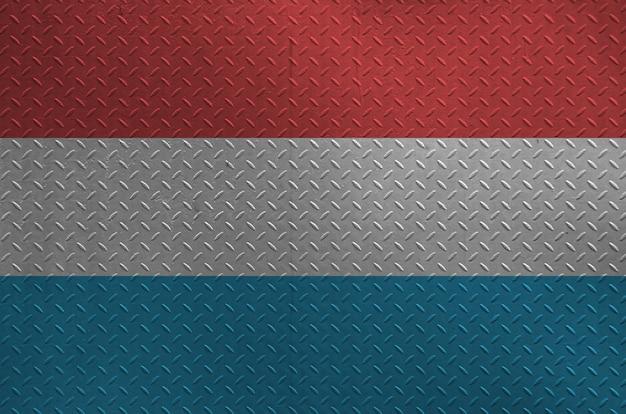 Bandeira de luxemburgo representada em cores de tinta na placa de metal escovada velha ou parede closeup. banner texturizado em fundo áspero