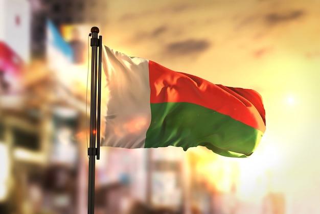 Bandeira de madagascar contra a cidade fundo borrado no amanhecer luz de fundo