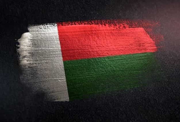 Bandeira de madagáscar feita de tinta pincel metálico na parede escura de grunge
