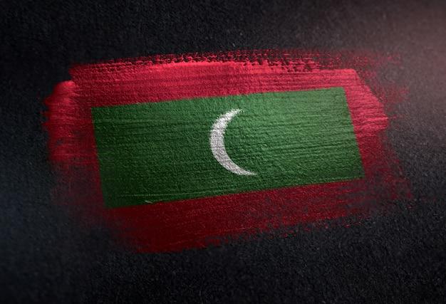 Bandeira de maldivas feita de tinta de pincel metálico na parede escura de grunge