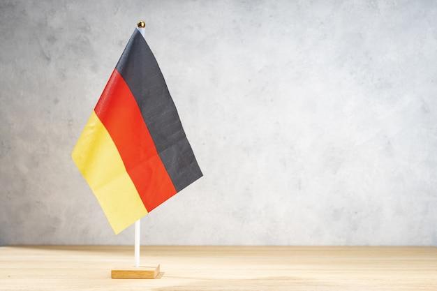 Bandeira de mesa da alemanha na parede texturizada branca. copie o espaço para texto, projetos ou desenhos