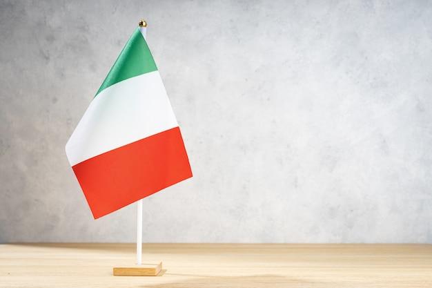Bandeira de mesa da itália na parede texturizada branca. copie o espaço para texto, projetos ou desenhos
