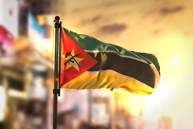 Bandeira de moçambique contra a cidade fundo borrado no amanhecer luz de fundo