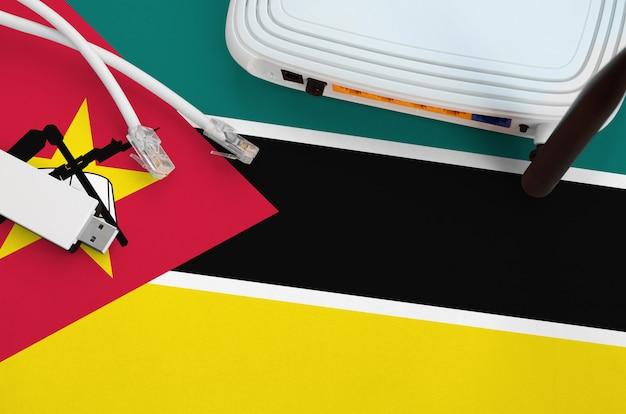 Bandeira de moçambique, retratada na tabela com o cabo rj45 da internet, adaptador sem fio usb wifi e roteador. conceito de conexão à internet