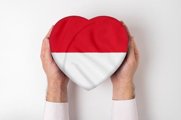 Bandeira de mônaco em uma caixa em forma de coração nas mãos masculinas.