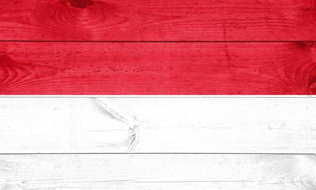 Bandeira de mônaco no fundo horizontal de madeira.