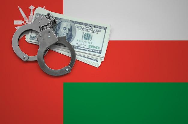 Bandeira de omã com algemas e um pacote de dólares. o conceito de infringir a lei e crimes de ladrões