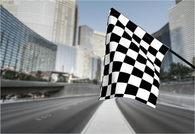 Bandeira de ondulação quadriculada no fundo da cidade. foto do conceito do vencedor
