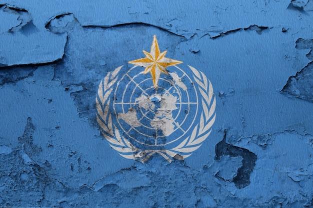 Bandeira de organização meteorológica mundial pintada na parede rachada do grunge