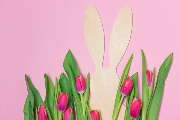 Bandeira de páscoa com figura de coelho de madeira e tulipas frescas roxas. copie o espaço para texto