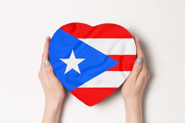 Bandeira de porto rico em uma caixa em forma de coração nas mãos femininas