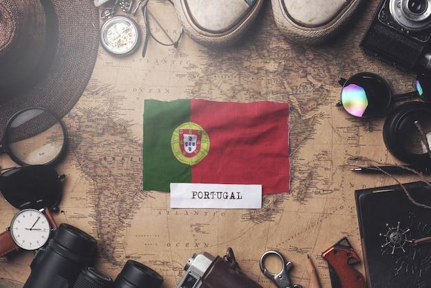 Bandeira de portugal entre acessórios do viajante no antigo mapa vintage. tiro aéreo