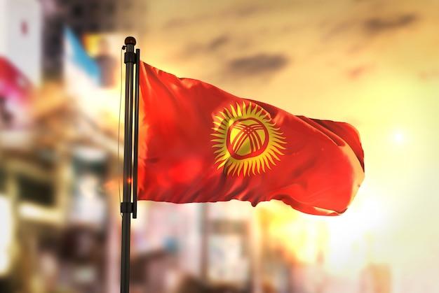 Bandeira de quirguistão contra a cidade fundo borrado no amanhecer luz de fundo