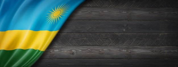 Bandeira de ruanda na parede de madeira preta. banner panorâmico horizontal.