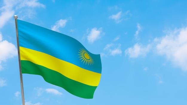 Bandeira de ruanda na pole. céu azul. bandeira nacional de ruanda