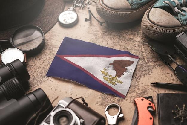 Bandeira de samoa americana entre acessórios do viajante no mapa antigo do vintage. conceito de destino turístico.