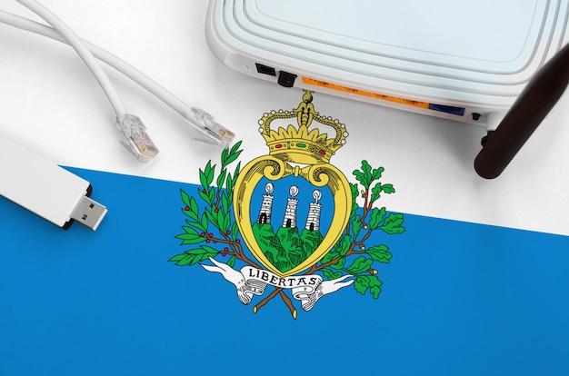 Bandeira de san marino, retratada na mesa com cabo de internet, adaptador sem fio usb wifi e roteador. conceito de conexão à internet