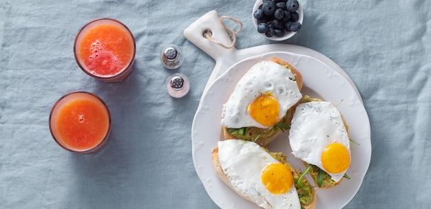 Bandeira de sanduíche de abacate e ovo frito com páprica em cima da mesa. saudável café da manhã ou lanche em um prato numa toalha de mesa de linho azul e suco de laranja espremido na hora