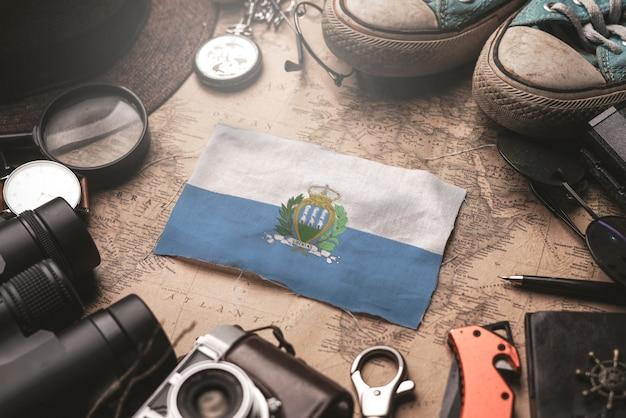 Bandeira de são marinho entre acessórios do viajante no antigo mapa vintage. conceito de destino turístico.