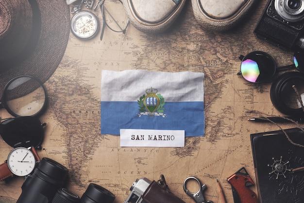 Bandeira de são marinho entre acessórios do viajante no antigo mapa vintage. tiro aéreo