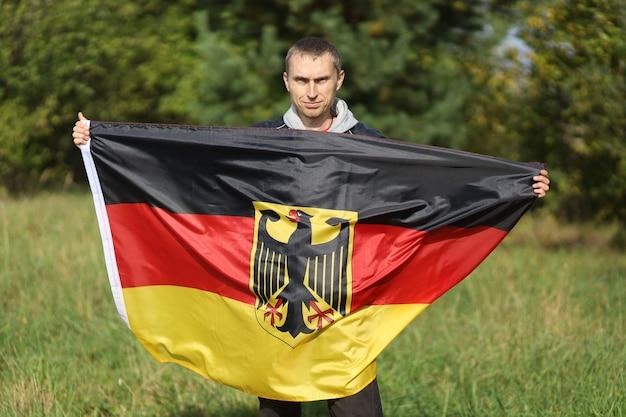 Bandeira de seda da alemanha nas mãos do homem