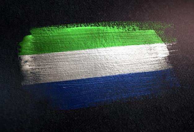 Bandeira de serra leoa, feita de tinta de pincel metálico na parede escura de grunge
