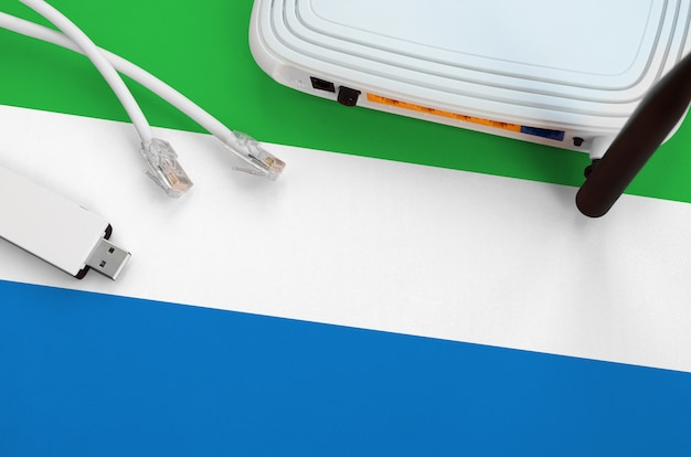 Bandeira de serra leoa, retratada na tabela com o cabo rj45 da internet, adaptador sem fio usb wifi e roteador. conceito de conexão à internet