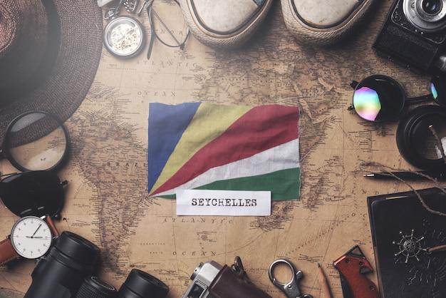 Bandeira de seychelles entre acessórios do viajante no mapa antigo do vintage. tiro aéreo