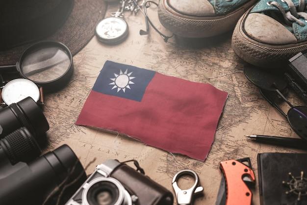Bandeira de taiwan entre acessórios do viajante no antigo mapa vintage. conceito de destino turístico.