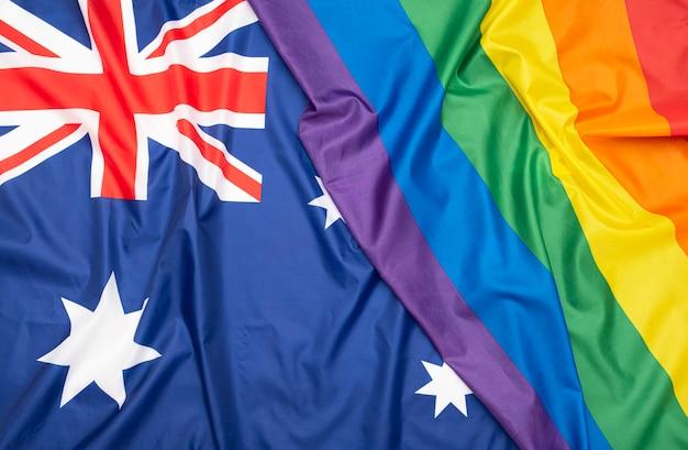 Bandeira de tecido natural da austrália e bandeira lgbt do arco-íris como textura ou plano de fundo, imagem conceitual sobre direitos humanos