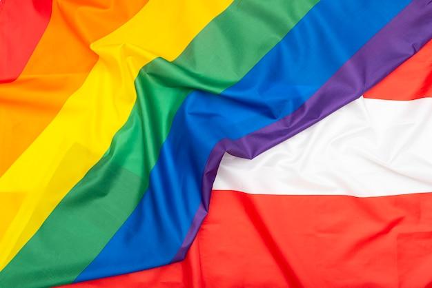 Bandeira de tecido natural da áustria e bandeira lgbt do arco-íris como textura ou plano de fundo, imagem conceitual sobre direitos humanos