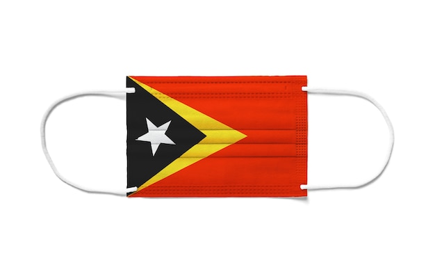 Bandeira de timor leste em uma máscara cirúrgica descartável. superfície branca isolada