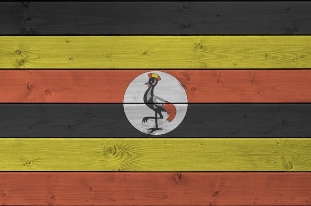 Bandeira de uganda, retratada em cores brilhantes de tinta na parede de madeira velha.