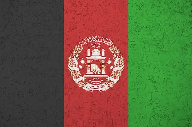 Bandeira do afeganistão, representada em cores brilhantes de tinta na parede de reboco em relevo antigo. banner texturizado em fundo áspero