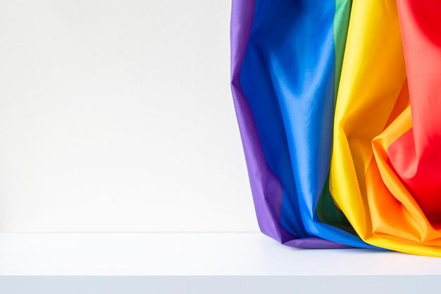 Bandeira do arco-íris e mesa branca, interior da sala. bandeira gay na parede, imagem conceitual, espaço para texto.