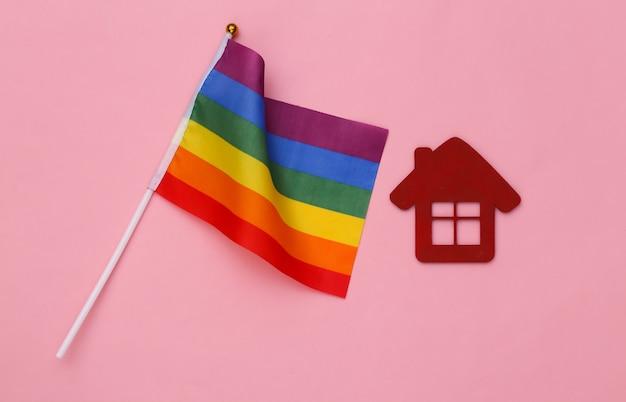 Bandeira do arco-íris lgbt e casa em fundo rosa. tolerância, liberdade