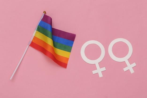 Bandeira do arco-íris lgbt e dois símbolos femininos em um fundo rosa. relacionamentos lésbicos. tolerância