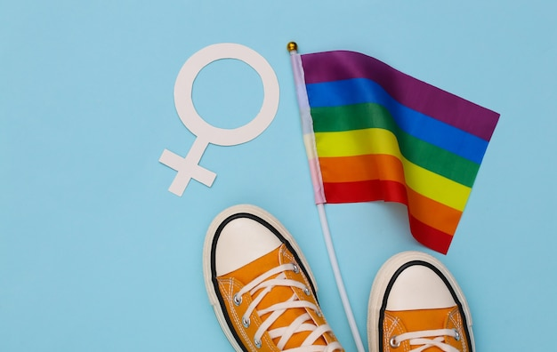 Bandeira do arco-íris lgbt e tênis, símbolo feminino sobre fundo azul. tolerância, liberdade, parada gay. vista do topo