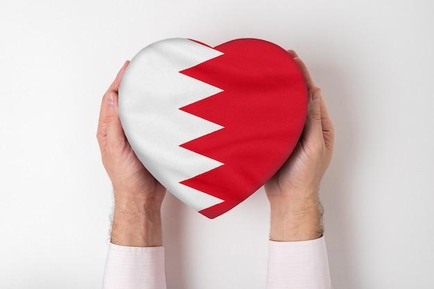 Bandeira do bahrein em uma caixa em forma de coração nas mãos masculinas.