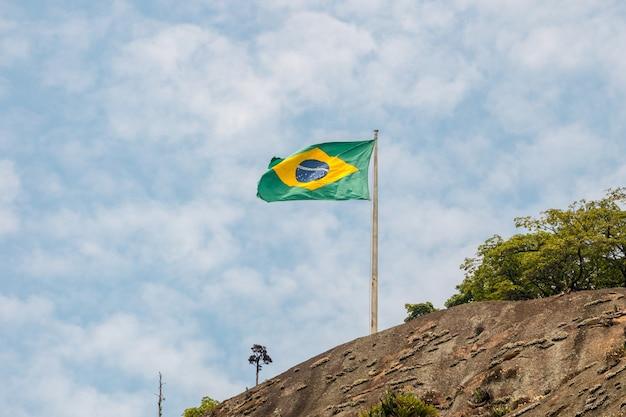 Bandeira do brasil ao ar livre com um lindo céu azul no rio de janeiro.