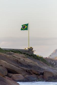 Bandeira do brasil no topo de uma rocha na praia do diabo