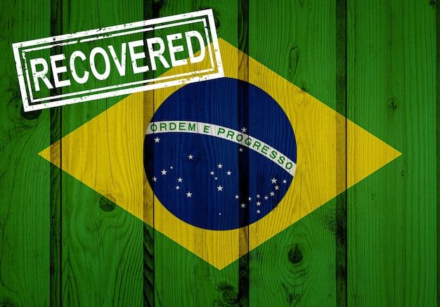 Bandeira do brasil que sobreviveu ou se recuperou de infecções de epidemia de vírus corona ou coronavírus. bandeira do grunge com selo recuperado