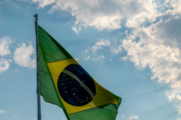 Bandeira do brasil tremulando ao vento. bandeira brasileira com céu azul e nuvens brancas.