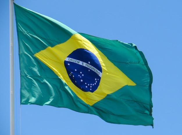 Bandeira do brasil tremulando ao vento. no centro da bandeira com as palavras