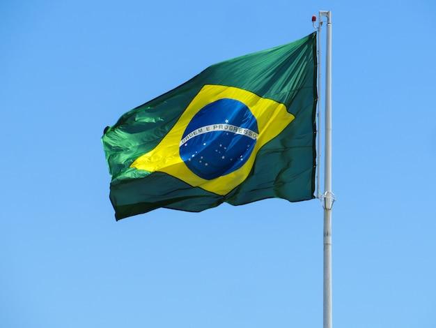 Bandeira do brasil tremulando ao vento. no centro da bandeira com as palavras ordem e progresso