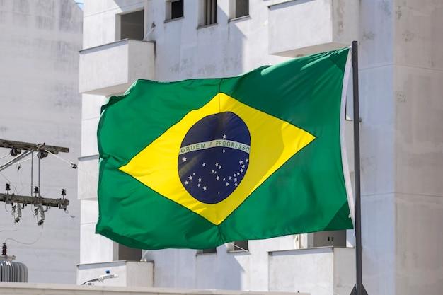 Bandeira do brasil tremulando ao vento. ordem e progresso, em português. bandeira brasileira