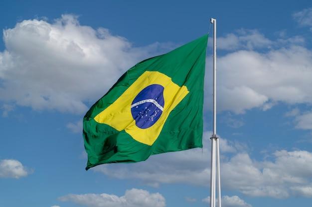 Bandeira do brasil tremulando no céu azul com nuvens bandeira do brasil