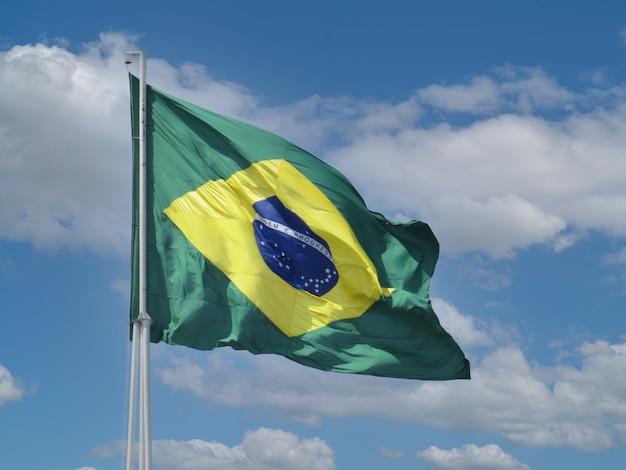 Bandeira do brasil tremulando no céu azul com nuvens ordem e progresso em português brasileiro