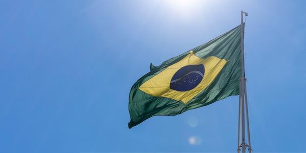 Bandeira do brasil tremulando no céu azul com raios de sol ordem e progresso na brasilia portuguesa