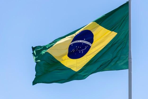 Bandeira do brasil tremulando no céu azul ordem e progresso na bandeira luso-brasileira